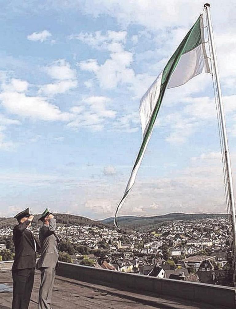 Stefan Immekus und Georg Arens (v. l.) hissten gestern Abend hoch über Olpe die Fahne als weithin sichtbares Zeichen: Das Schützenfest hat begonnen. Foto: hobö