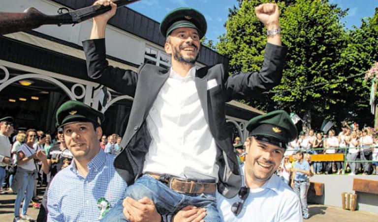 Die beiden Korporalschaftsführer der Zweiten Ralf und Jörg Muckenhaupt tragen Stephan Neuhaus zum Rotweintisch. Foto: Nicole Voss